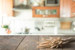Dessus de table en bois avec du blé sur le fond de pièce de cuisine de tache floue pour le produit de montage Photographie stock