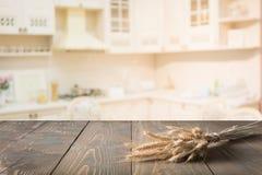Dessus de table en bois avec du blé sur le fond de pièce de cuisine de tache floue pour le produit de montage Image libre de droits