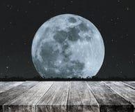 Dessus de table en bois avec la belle pleine lune la nuit avec les étoiles et la pelouse en verre de silhouette Fond de pleine lu Images libres de droits