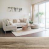 Dessus de table en bois avec la tache floue de l'intérieur moderne de salon Photos libres de droits