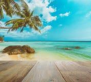 Dessus de table en bois avec la tache floue de la belle plage tropicale Photos stock