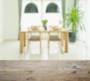 Dessus de table en bois avec la tache floue de la table de salle à manger et des chaises Images stock