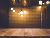 Dessus de table en bois dessus brouillé de la contre- boutique de café avec l'ampoule Photo stock