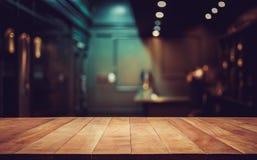 Dessus de table en bois dessus brouillé de la contre- boutique de café avec l'ampoule Photo libre de droits