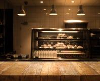 Dessus de table en bois dessus brouillé de la contre- boutique de café avec l'ampoule image stock