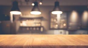 Dessus de table en bois dessus brouillé de la contre- boutique de café avec le fond d'ampoule Images stock