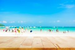 Dessus de table en bois sur le fond brouillé de plage avec des personnes dans des vêtements colorés Photo stock