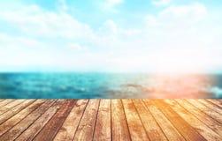 Dessus de table en bois sur le fond de mer de tache floue Photographie stock