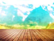 Dessus de table en bois sur le fond de montagnes de tache floue Photographie stock libre de droits
