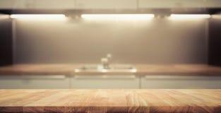 Dessus de table en bois sur le fond de pièce de cuisine de tache floue Images stock