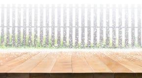 Dessus de table en bois vide avec des chutes de neige de saison d'hiver sur la barrière Image stock