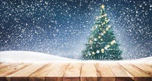 Dessus de table en bois vide avec l'arbre de Noël et chutes de neige en ciel Image libre de droits