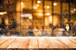 Dessus de table en bois vide avec les chutes de neige et le restaurant de café de bokeh Photo stock