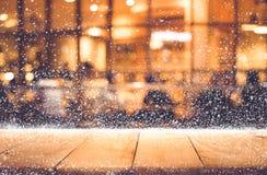 Dessus de table en bois vide avec les chutes de neige et le restaurant de café de bokeh Photographie stock
