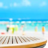 Dessus de table ronde sur le fond de plage de tache floue avec des personnes dans des vêtements colorés Photos stock