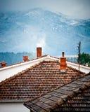 Dessus de toit avec les cheminées de fumage en hiver photos libres de droits