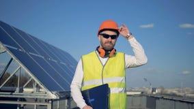 Dessus de toit avec un panneau solaire et un ingénieur soulevant son masque là-dessus banque de vidéos