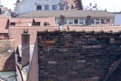 Dessus de toit carrelés rouges dans une ville avec des antennes Photographie stock