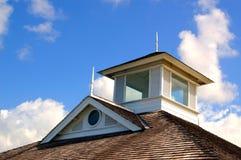 Dessus de toit de bardeau contre un ciel nuageux Photographie stock