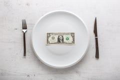Dessus de vue un billet de banque du dollar du plat blanc avec la fourchette et le kni Photos stock