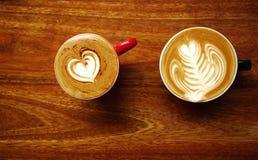 Dessus deux de tasse de café chaude d'art de latte sur le CCB en bois de table de brun foncé Photographie stock