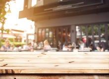 Dessus du compteur en bois de table avec les personnes brouillées dans le café photo stock