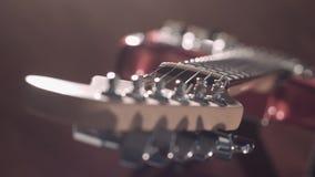 Dessus en bas de décalage de foyer sur la guitare électrique sur un support, bokeh cinématographique banque de vidéos