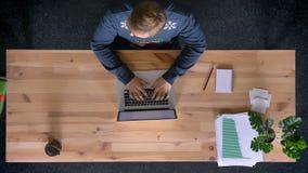 Dessus en bas de la vue de l'homme travaillant dans le bureau devant l'ordinateur portable, étant présenté un grand boîte-cadeau  clips vidéos