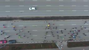 Dessus en bas de tir aérien des marathoniens de ville concurrençant sur la route vide banque de vidéos