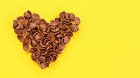 Dessus en bas de vue, cornflakes de chocolat au conseil jaune disposé dans la forme du coeur, l'espace pour le texte du côté droi photographie stock libre de droits