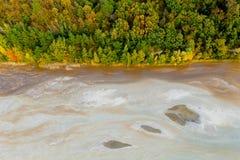 Dessus en bas de vue sur des riches de rivière en déchets minéraux de centrale, écoulements le long du mur de forêt photos libres de droits