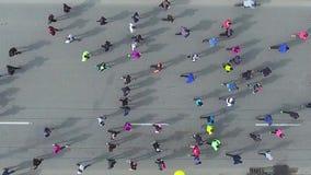 Dessus en bas du tir aérien des marathoniens sur la route goudronnée banque de vidéos