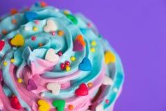 Dessus multicolore crémeux de petit gâteau de plan rapproché avec les coeurs colorés et Photographie stock libre de droits