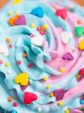 Dessus multicolore crémeux de petit gâteau de plan rapproché avec les coeurs colorés et Photo libre de droits