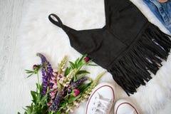 Dessus noir de suède avec la frange sur la fourrure blanche, un bouquet des fleurs, espadrilles concept à la mode Photo stock