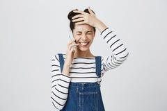 Dessus rayé de port de brune de fille gaie attirante d'étudiant, serrant des dents dans le sourire joyeux, parlant au téléphone i photographie stock