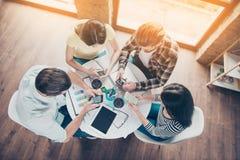 Dessus-vue de quatre étudiants s'asseyant par la table utilisant leur futé Photographie stock libre de droits