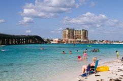 Destin Bridge Vacationers. Tourists vacationing is Destin, Florida swim and relax in the clear blue waters of the pass with a veiw of the bridge and the harbor royalty free stock photo