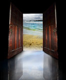 Destination. Two wooden  doors open to reveal a sandy beach and lagoon.  Concept for vacation or travel.  You could easily cut out the beach scene and add your Royalty Free Stock Photos