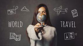 The Destination Chosing. Beautiful long-haired girl is holding small globe on grey background with travel icons, destination chosing concept Royalty Free Stock Photo