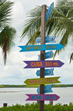 Destination signs with direction and milage. On a wood post on a tropical island Stock Photos