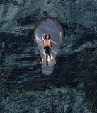 Destination successfully achieved. The concept of destination successfully achieved. Woman hiker jumping on a hole shapped as a key into the rock wall. The stock images