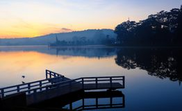 Small bridge reflect on lake at sunrise. Destination for Vietnam travel at Da Lat city, mist evaporate from surface water of lake, silhouette of small bridge Royalty Free Stock Image