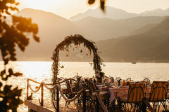 Destination wedding arch and banqouet covered table at sunset Stock Photos