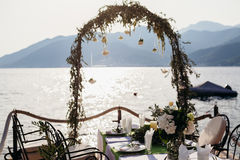 Destination wedding arch and banqouet covered table at sunset Royalty Free Stock Photo