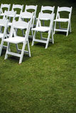 Destination Wedding. Foldable wedding chairs are set out in a pattern on tropical grass, waiting for wedding guests to arrive Stock Photos