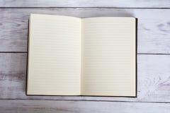 Destinerad tidskriftsbok för klassiskt läder som är öppen på ett vitt ladugårdbrädegolv Royaltyfria Bilder