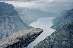 Destino famoso Trolltunga del senderismo en Odda, Noruega, durante el día lluvioso con las nubes en el cielo Fotos de archivo libres de regalías