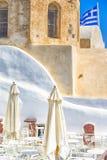 Destinos de surpresa do curso Ar livre Caffee na vila de Oia na ilha de Santorini em Grécia Pale Church idoso no fundo imagem de stock royalty free