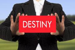 Destiny. Businesswoman in a black jacket shows a card with the inscription destiny. Selective focus stock image